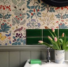 Emerald beveled subway tiles and printed botanical wallpaper in the London home of Luke Edward Hall.
