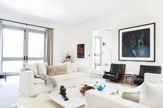 Bright and white living space with cozy leather armchairs and oversized artwork