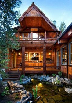 Wood cabin home with water feature in the front
