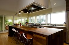 1950 ranch in Vancouver: a large island takes center stage, and a sliding door and sidelights bring the outdoors in.would love big windows in the kitchen Upper Cabinets, Wood Cabinets, Entry Doors, Sliding Doors, Exterior Remodel, Ranch Exterior, Brown Kitchens, Big Windows, House Built