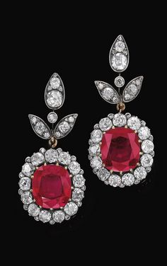 PAIR OF VERY IMPORTANT RUBY AND DIAMOND PENDENT EAR CLIPS Each suspending a cushion-shaped ruby, weighing 11.46 and 11.64 carats respectively, set within a surround of cushion-shaped and circular-cut diamonds, to a surmount of foliate design embellished with similarly cut and rose diamonds, screw back fittings. ( Sold for 3.3 million...)