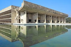Chandigarh, the utopian city designed by Le Corbusier with Pierre Jeanneret in 1947, in post-independence India, was built largely out of concrete. In the Palais de l'Assemblée, situated on a reflecting pool, the swooping sculptural form at the entrance contrasts with the building's linear concrete columns throughout.
