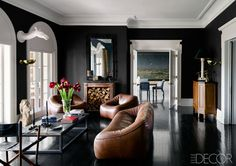 In this grand home in Tuxedo Park, New York, a pair of French doors connect the moody, masculine sitting room with the sprawling lawn outside. The 1970s leather sofa and chairs in another sitting room are by Gerard van den Berg for Montis, the marble top of the cocktail table came from a Belgium chocolate factory, and the camel sculptures were bought on 1stdibs. Tour the rest of the home.