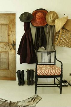 hats, rustic door, black painted chair, baskets....perfect.