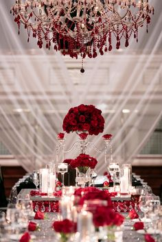 red floral centerpieces surrounded by candles