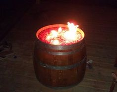 "Wine barrel turned into a propane fire pit. 20lb propane bottle underneath, and its on hidden wheels so that we can roll it around to anyplace on the deck with ease. I used red-orange fire glass and have the burner and glass counter-sunk into the barrel head with a 2"" deep metal pan. Total cost under 500$. When not used as a fire pit a table top can be put over it."