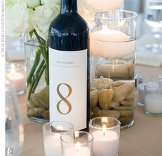 For the centerpieces, Michelle topped water- and rock-filled vases with floating candles. Bottles of wine showed off the table numbers. Mich...