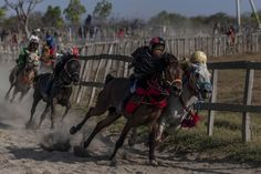 ULET IFANSASTI—GETTY IMAGES Sept. 27, 2014. Child jockeys compete during the traditional horse races as part of Moyo festival in Sumbawa Island, West Nusa Tenggara, Indonesia. The racing tradition involves child jockeys who ride bareback