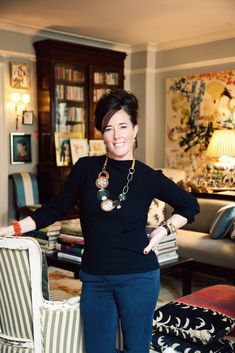 Kate Spade at home. secretary filled with books, framed art sitting in front of doors