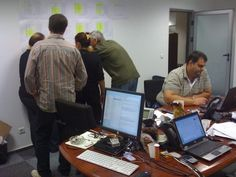 """The """"control room"""" pictured here on the rollout weekend of the big-bang data-migration of ca 1 million debit cards from a legacy card system into a new card system for a commercial bank in Romania. The management team is looking at the migration activity plan to verify a step in the process. Submitted by Fotis Panagiotou."""