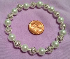 Stretch bracelet with white glass pearl beads, silver filigree beads, and silver spacer beads $18