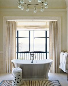 Airy and bright, this soft toned master bathroom offers a great place to relax. The stainless steel tub positioned against the casual window treatment and mellow colors provides an unexpected combinat