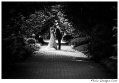 A bride and groom share a kiss in the sunlight at Olbrich Botanical Gardens in Madison, Wi