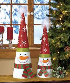 Add some sparkle to your home with the 2-Pc. Tree-Shaped Holiday Decor. Glittery metal cones feature bright and iconic designs. Each is topped with a fuzzy, whi