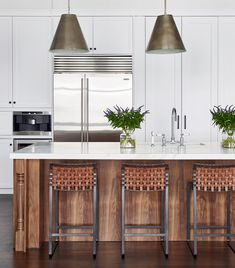 A kitchen is centered by a walnut island topped with Calacatta gold marble | archdigest.com