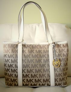 The Michael Kors East West Large Signature Jacquard Tote is Practical and Poised for Work or Play. This Roomy Tote is an Everyday Essential. Made from Durable Canvas, Sturdy Leather Straps and Plenty of Pockets, it's Ideally Sized to Hold All of Your Essential Items. The Gold Tone Accents Agains...