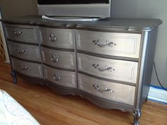"""Old wood dresser gets new life with Martha Stewart precious metal paints.   To achieve this look we used Martha Stewart's """"Quayside"""" on everything but the drawers.  For the drawers we used Martha Stewart's """"mirror glass"""" paint.  The old brown handles even received paint treatment with silver spray from a can."""