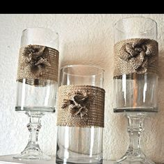 Simple cylinder vases glued on to glass candle sticks and embellished with a wide strip of burlap and a burlap flower. I would use 2 contrasting colors of burlap to add interest.