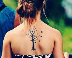 A barren tree, but with birds circling around it - tattoo