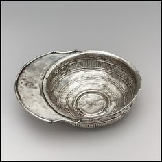 Silver Drinking Bowl with Handle Date: 700s Geography: Made in Tirana Culture: Avar Medium: Silver Dimensions: 2 × 9 15/16 × 7 5/16 in., 9.613 Troy Ounces (5.1 × 25.2 × 18.5 cm, 299g) Other (diameter of cup only): 7 5/16 in. (18.5 cm)