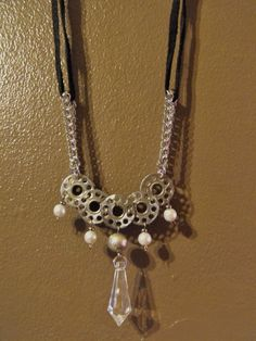 I used old metal sewing bobbins and some faux pearls, and a chandelier crystal to make this one of a kind necklace