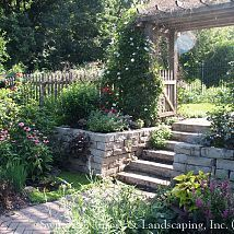 From Hometalk- love the way the landscape designer took  a negative- a sloping yard and made it a positive. An arbor and stone hardscape divide the upper lawn from the lower lawn and make a beautiful focal point.