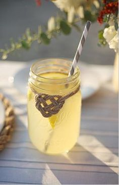 Sailor's heart knot tied around a mason jar with lemonade and vintage striped straw.