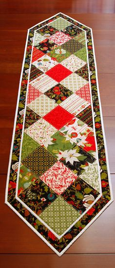 Holiday Table Runner made from Moda Fabrics Tole Christmas collection.  This festive runner measures 60 x 16 inches from point to point.