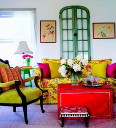 The red, blue-green, and yellow-green in this living room is an example of a split-complementary color scheme. This creates a more intense feeling.