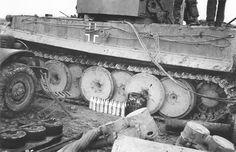 A Tiger 1 having some major field repairs made. Note the air filter assemblies laying on the ground along with the intake manifold from the V-12 Maybach HL 210 P45 first generation aluminum engine block assembly