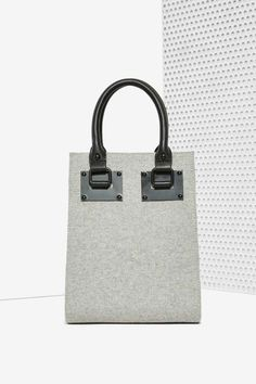The Rock the Tote Mini Bag comes in structured gray felt and features a mini tote shape, black metal hardware, vegan leather handles, metal hardware, zip closure and an adjustable vegan leather strap.