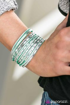 A band of minty green suede is spliced into six glistening strands and decorated with white rhinestones, glassy emerald-cut gems, and flat silver cube beads. The elongated design allows for a trendy double wrap around the wrist. Features an adjustable snap closure.   Sold as one individual bracelet.