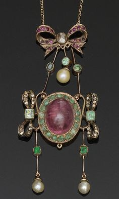 A Continental vari gem-set pendant  The central oval cabochon ruby and emerald cluster between two emerald and rose-cut diamond set ribbon bow motifs, below a similarly set surmount of conforming design, suspending two emerald and pearl drops below, on a fine curb-link chain, (break to pendant, pearls untested), pendant length 7cm.