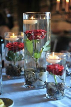 Beautiful easy DIY centerpieces WITH white roses and blues stones on the bottom floating candle on top !!!! yessss!