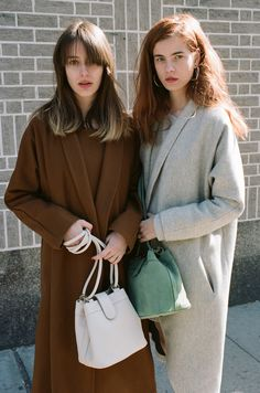 Datura Blog - East Village Girls Andrea wearing the Rust Kimono Coat and Zaga Wearing the Tusk Ivory Escape Coat. Both with matching sweater dresses.
