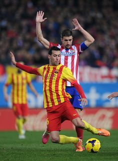 Sergio Busquets (L) of FC Barcelona clears the ball in front of Gabiel Fernandez 'Gabi' of Club Atletico de Madrid during the La Liga match between Club Atletico de Madrid and FC Barcelona at Vicente Calderon Stadium on January 11, 2014 in Madrid, Spain.