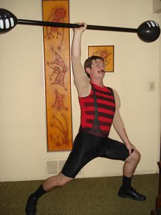 Strong man DIY costume. Bicycle shorts w/straps.  Red tank w/spray painted lines. Foam-stuffed pantyhose worn as a top (w/crouch cutout). Dumbbell made from black balloons (painted #'s) and dowel core fabric roll (painted black). Velco mustache (fuzzy side). Curled slick hair.