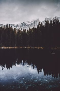 Glacial mountains reflecting in an icy lake with a beautiful horizon of coniferous trees