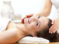 Portrait of a cheerful young female receiving facial massage