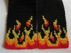 Handmade, mens black scarf. The scarf is crocheted in black with red, orange, and yellow flames at the bottom edge of the scarf. The flames look the same from both sides of the scarf. The last photograph shows the back of the scarf. Scarf measures approximately 5 1/2 inches (14 cm) wide and 66 inches (1.68 m) long. Fringe is optional and if you would like fringe added please include a note to me at checkout. Scarf is crocheted with a high quality, very soft acrylic yarn. This scarf is m...