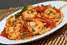 Shrimp Linguine in a Tomato and White Wine Sauce1 tablespoon olive oil 1 onion, diced 4 cloves garlic, chopped chili flakes to taste 1/4 cup white wine 1 (28 ounce) can plum tomatoes, crushed 1/2 teaspoon oregano salt and pepper to taste 1 pound shrimp, peeled and deviened 1/2 cup fresh herbs such as parsley and basil, chopped 1 pound linguine (I used whole wheat)