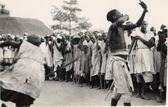 "Nigeria [?], ""scenes at a Fulani flogging ceremony"" or ""the Shadi dance"". Two adult males surrounded by crowd of male and female adults and children. Males wearing trousers, cloth, personal-ornaments. Male at left brandishing stick [?], male at right holding object aloft. Crowd wearing cloths, head-gear. Outdoor setting, wall [?] in background. Medium: Gelatin silver print."