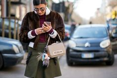 Brown fur jacket with white collar and cuffs worn with an olive green skirt with embellishments on pockets // MFW... | Street Style