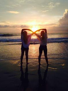 amigas haciendo signo infinito en la playa