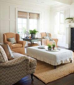Slipcovered chairs and a National Upholstery sofa surround the Lee Industries ottoman in this California farm home.