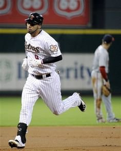 Houston Astros' Marwin Gonzalez (9) rounds the bases on a solo home run as Washington Nationals' Danny Espinosa looks to the outfield in the first inning of a baseball game, Monday, Aug. 6, 2012, in Houston. (AP Photo/Pat Sullivan)