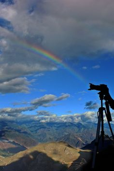 Silhouette of Man Holding Camera on Tripod With Mountain and Rainbow on…