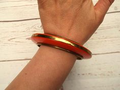 Awesome vintage chunky statement bangle  Circa 1970s  Bright tangerine orange with a brass inlay and insert  Lovely heavy quality  Measurements were taken from the inside of the bangle and outside around the width of the dome height  It has some signs of wear but nothing majar  This bangle would look fabulous and stylish stacked with wood bangles, contrast plastic or even other brass bangles Free UK postage Please find other jewellery items here https://www.etsy.com/shop/f...