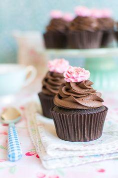 En la vídeo receta de esta semana, os voy a mostrar cómo hacer unos chocolateados cupcakes decorados con una mini rosa de fondant. Estos cupcakes están muy jugosos y con un intenso sabor a chocolate! Toda una delicia para los que nos encanta este ingrediente tan deseado. Para que el cupcake quede bien jugoso, añado buttemilk a la masa del bizcocho. Es un truco muy fácil que le da una textura especial. Además utilizo cacao en polvo puro para que el sabor sea muy intenso. Para la buttercream…
