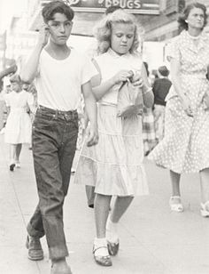 1940s vernacular sidewalk snapshot of handsome young Portuguese immigrant boy in rolled up Levis jeans talking on imaginary cellphone as he proudly strolls down California Central Valley sidewalk with babyface blonde American girlfriend. vernacular photo snapshot-www.reservatory.net